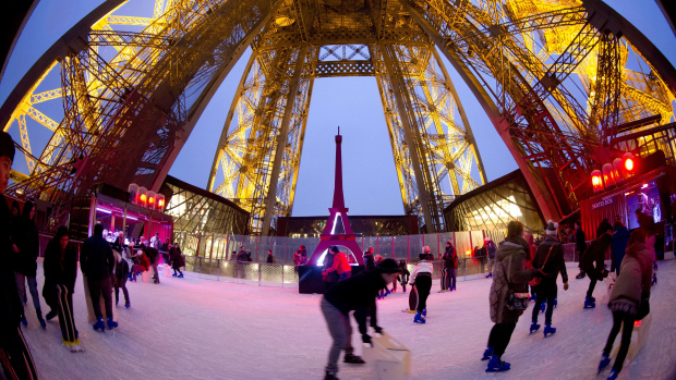 People skate on the ice rink hosted on the eiffel tower's first floor on December 15, 2014 in Paris. AFP PHOTO / KENZO TRIBOUILLARD (Photo credit should read KENZO TRIBOUILLARD/AFP/Getty Images)