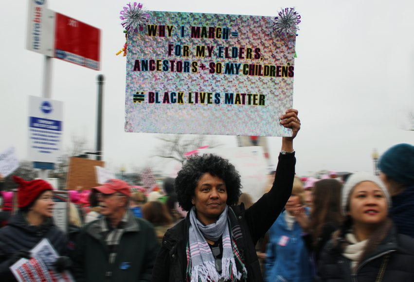 """One woman displays her sign """"Why I march = For My Elders, Ancestors + So My Children's #Black Lives Matter"""