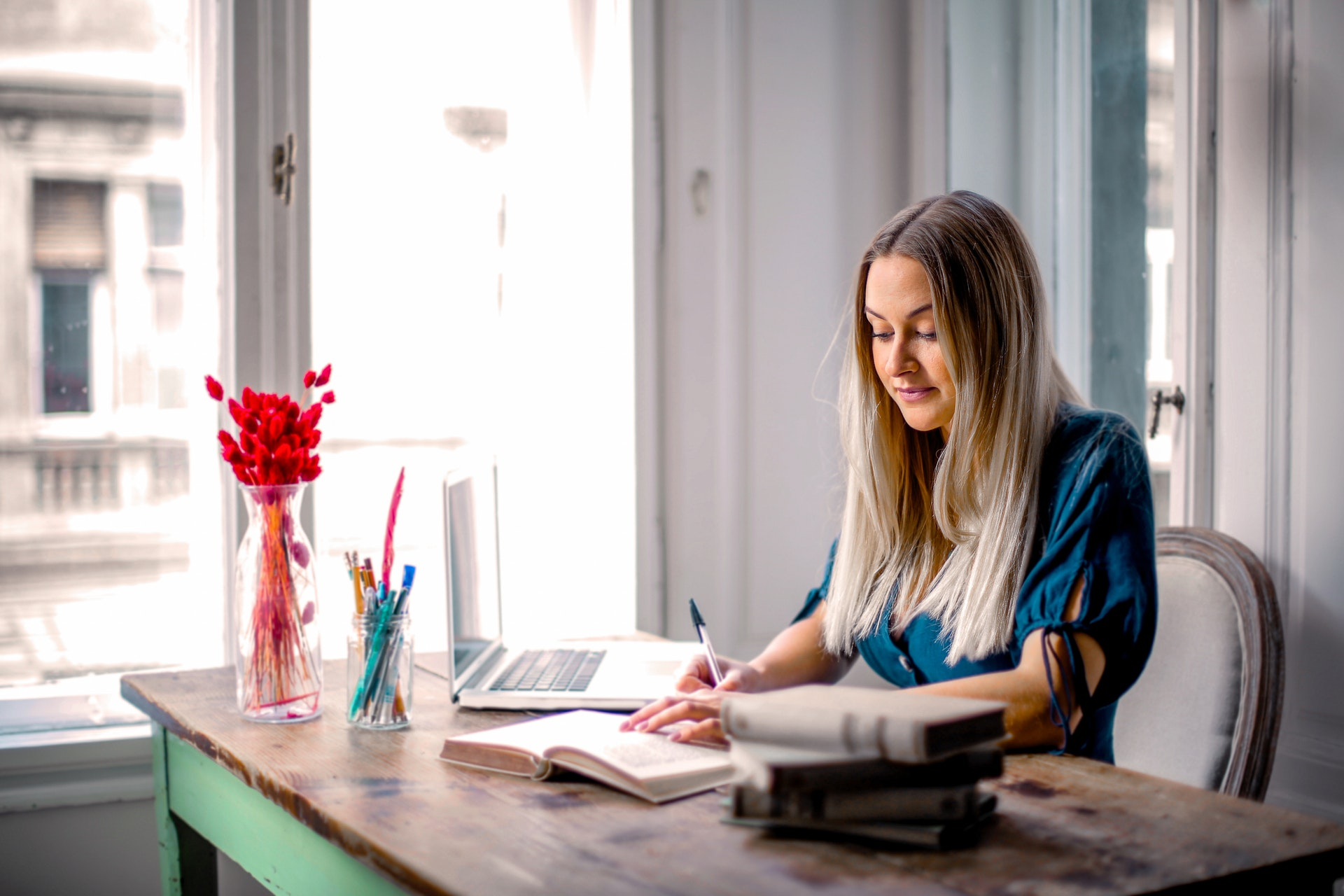 woman-in-blue-long-sleeve-shirt-sitting-at-the-table-working-3767388