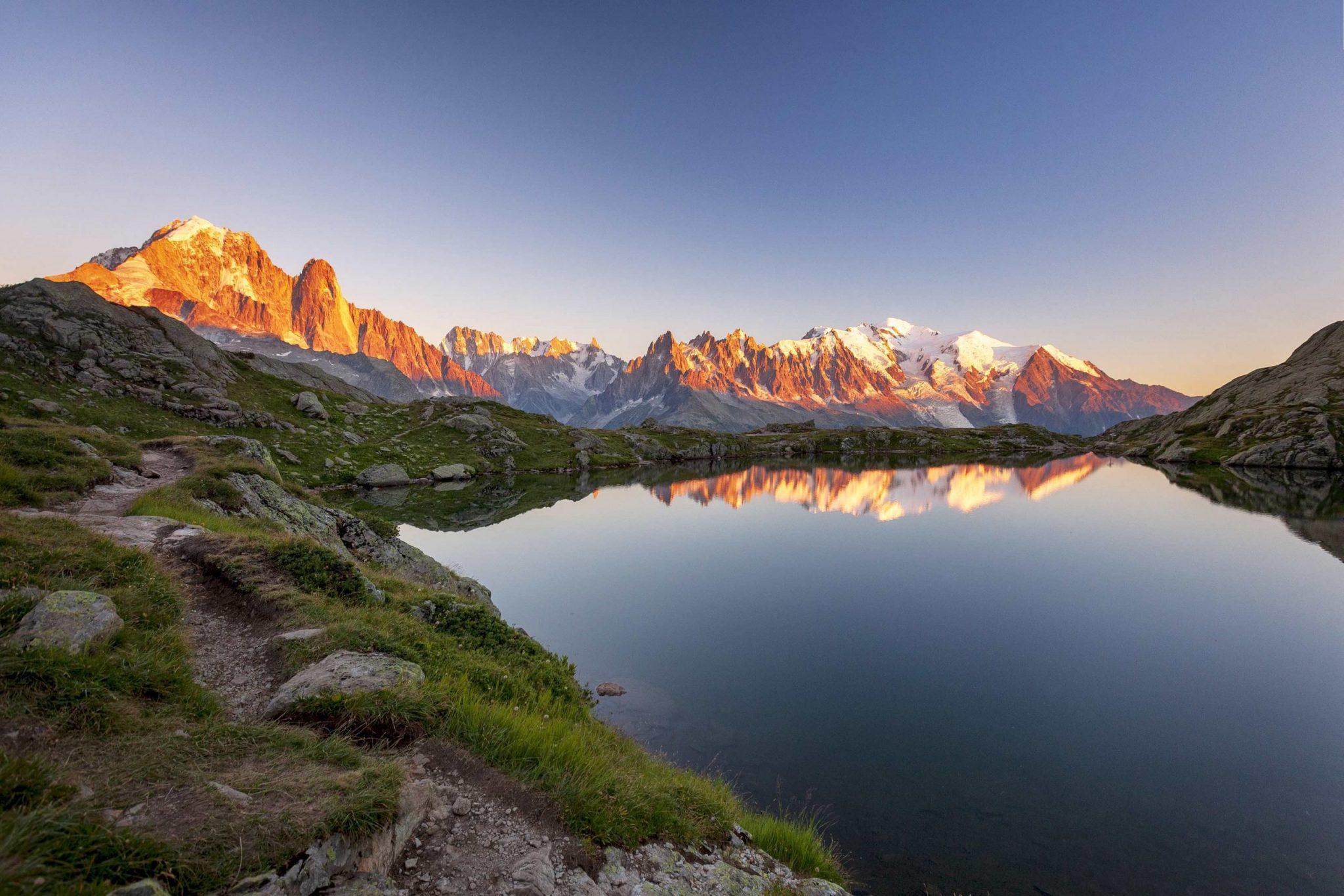 Hikers on the shore of Lac des Chéserys admiring Mont Blanc massif, Chamonix, Haute Savoie, France