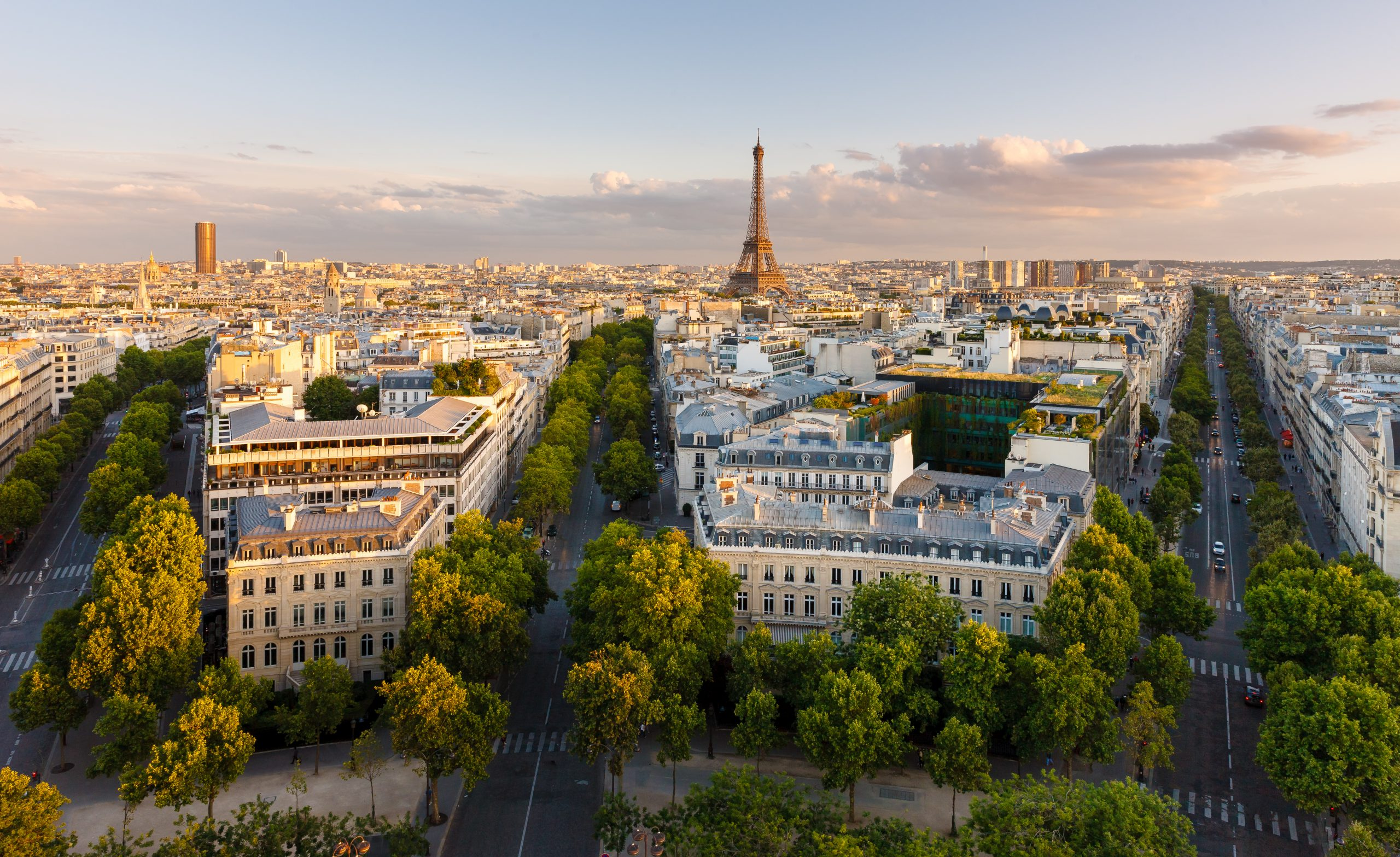 Paris from above showcasing the capital city's rooftops, the Eiffel Tower,  Paris tree-lined avenues with their haussmannian buildings and Montparnasse tower in the distance lit by the setting sun – Avenue Kleber, Avenue d'Iena and Avenue Marceau (16th arrondissement, Paris, France)