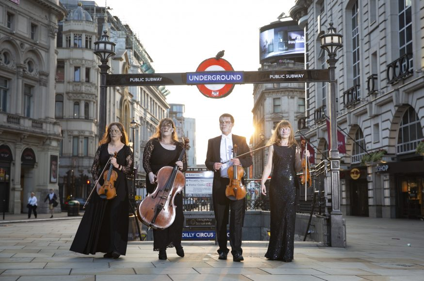 Morwenna Del Mar, Matthew Kettle, Esther King Smith and Fenella Humphreys, from Covent Garden Sinfonia orchestra's string quartet, perform a rendition of The Walking DeadÕs theme tune at Piccadilly Circus in London to celebrate the launch of the 11th and final season the show. Picture date: Monday August 16, 2021. PA Photo. The Covent Garden Sinfonia will perform as an ÔundeadÕ orchestra at the premiere of the first episode of the season at Kings Place Concert Hall on August 19 ahead of it airing on Star on Disney+ from August 23. Fans can enter a prize drawer to win tickets to the orchestral premiere, with entries open from today. Photo credit should read: Matt Alexander/PA Wire