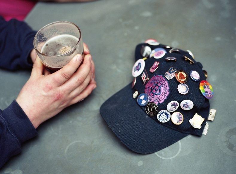 Two hands holding a pint next to a Dulwich Hamlet baseball cap covered with football pin badges ahead of the Dulwich Hamlet game against Truro City on the 16th March 2019 at Champion Hill in South London in the United Kingdom.(photo by Sam Mellish / In Pictures via Getty Images)